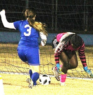 DeRidder's Courtney Craig (3) smacks the ball past South Beauregard keeper Ivana Robinson during the Lady Dragons' 2-0 win over the Lady K's on Thursday at Cecil Doyle Memorial Stadium.