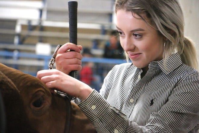 Ashtyn Adams, a 16-year-old Brownwood High School sophomore and member of the Brown County 4-H, stands with her 1,235-pound steer, Lizzorith, after winning Grand Champion Steer Friday at the Brown County Youth Fair.