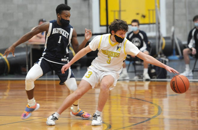 Guarded by Nantucket's Justin Bloise, left, Nauset's Andrew Berardi reaches for the ball during a double-overtime game won by Nauset on Tuesday.