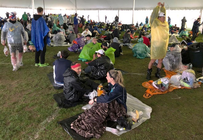 Runners wait under a tent while it rains before the start of the 123rd Boston Marathon in 2019. Organizers of the marathon, postponed indefinitely because of the coronavirus pandemic, have launched a virtual Athletes' Village to reproduce at least some of the camaraderie of the real thing.