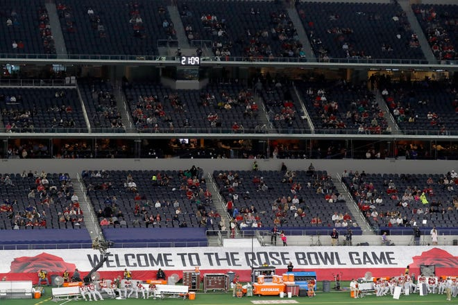 A banner along the sideline at AT&T Stadium welcomes fans as they watch the teams warm up before the Rose Bowl between Notre Dame and Alabama in Arlington, Texas, on New Year's Day.