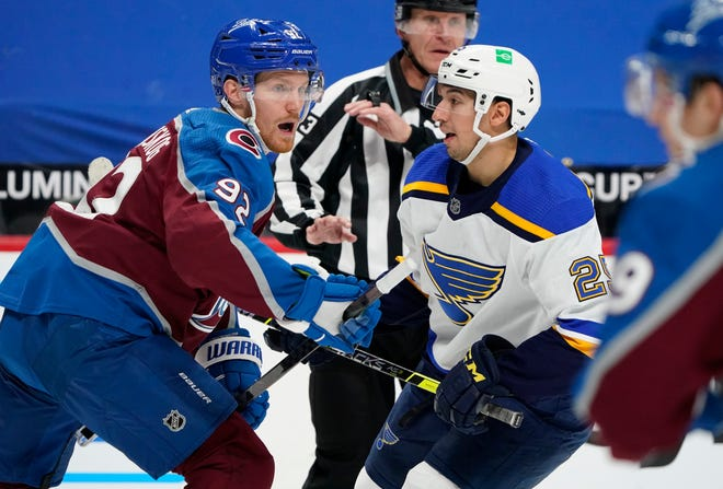 Colorado Avalanche left wing Gabriel Landeskog, left, pursues the puck with St. Louis Blues center Jordan Kyrou after a faceoff during a game Friday in Denver.