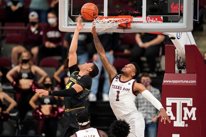 Missouri guard Javon Pickett (4) makes a basket as Texas A&M guard Savion Flagg (1) defends during a game Saturday in College Station, Texas.