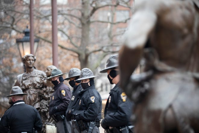 Members of the Ohio State Highway Patrol stand in front of the Ohio Statehouse where they will be on watch for the next 24 hours in Downtown Columbus, Ohio on January 16, 2021. The National Guard was also present in preparing for an armed protest that is anticipated to take place on Sunday, January 17.