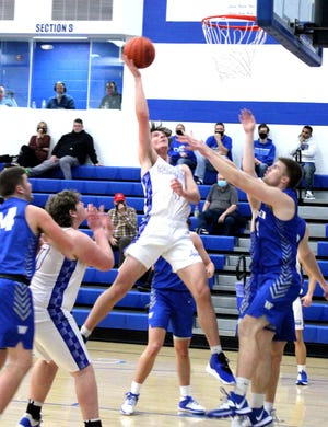 Cambridge's Sean Perkins (4) goes up high to score during Friday night's  game with Warren inside Gene Ford Gymnasium at Cambridge High School .