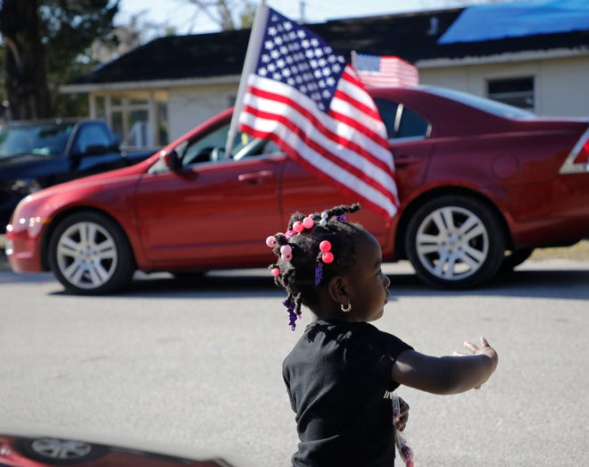 A young girl waves to cars driving past her Bunnell home Saturday morning during a motorized parade honoring civil rights leader Martin Luther King Jr. [NADIA ZOMORODIAN/NEWS-JOURNAL]