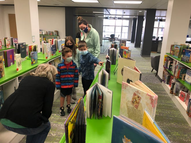 Hays Public Library assistant Kathy Pfeifer, left, on Saturday helps Megan Miller, Hays, right, and her children, left to right, Caiden, 4, Claire, 7, and Cole, 6, right, select books in the newly remodeled children's section on the second floor.