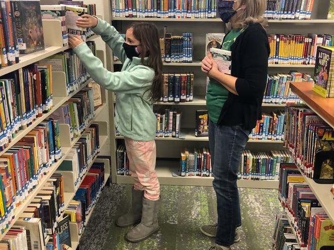 Hays Public Library assistant Kathy Pfeifer, right, on Saturday helps Claire Miller, 7, Hays, select books in the newly remodeled children's section on the second floor.