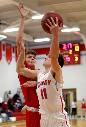 Trinity Catholic's Lucas Hammeke (11) drives to the basket past Moundridge's Logan Churchill (15) during their game Friday night. Moundridge defeated Trinity 58-39. Hammeke scored 21 points in the game.