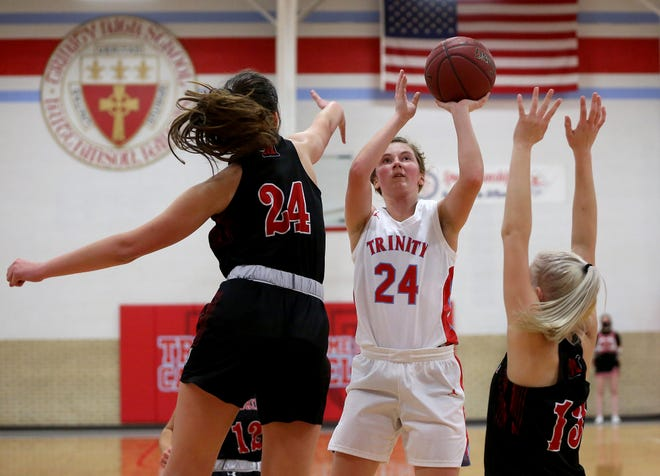 Trinity Catholic's Harley Hughes (24) shoots the ball past Moundridge's Kate Eichelberger (24) and Kindall Elmore (13) during their game Friday night, Jan. 15, 2021. Moundridge defeated Trinity 47-37. Hughes scored her 1,000th career point before halftime of the game. She finished the game with 19 points overall.