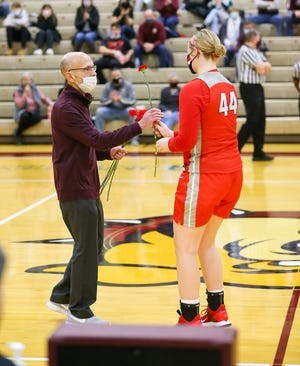 Mentor center Brooke Hickman presents Stow-Munroe Falls coach Bob Podges with a carnation before the Bulldogs' home game with the Cardinals Friday.