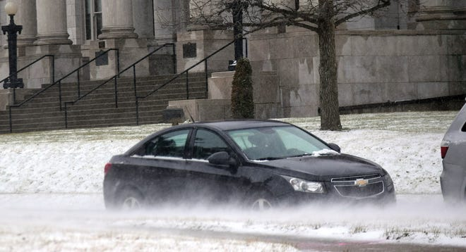Strong winds blow snow Friday in the area of the Leavenworth County Courthouse.