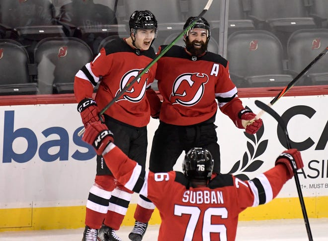 New Jersey Devils center Yegor Sharangovich (left) celebrates his game-winning overtime goal with right wing Kyle Palmieri and defenseman P.K. Subban (bottom) as the Devils defeated the Boston Bruins, 2-1, in an NHL hockey game Saturday in Newark, N.J.