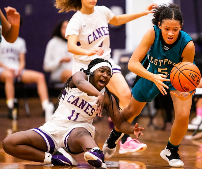 West Port's Joscelyn Mike steals the ball from Lake Weir's Nikaejah Green after Green loses the ball. The Wolf Pack defeated the Hurricanes, 42-25, Friday night.