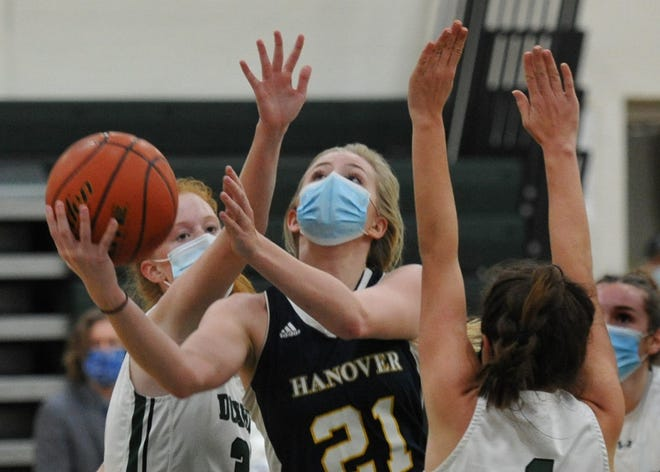 Hanover's McKalah Gaine, center, shoots for two as Duxbury's Amanda Donovan, left, and Lucy Laviolette, right, defend during girls basketball action at Duxbury High School, Friday, Jan. 15, 2021.