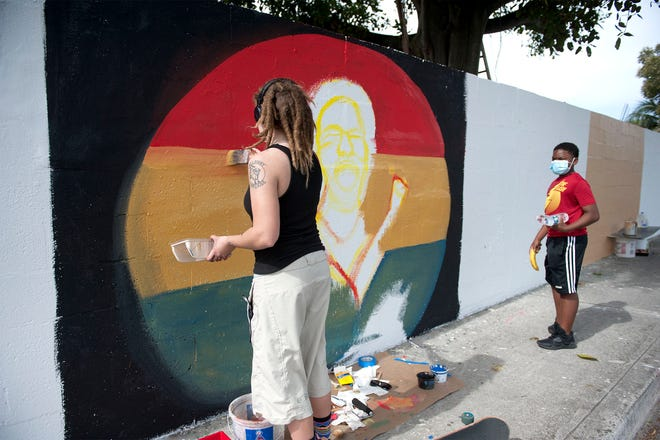 """Thaddeus Sinkfield, 12, right, watches as Caitlin Whitenton, both of Lake Worth, paints part of the Lake Worth Beach Unity Wall Saturday January 16, 2021 in Lake Worth Beach. """" I hope people don't spray paint over this. We've put a lot of heart into it,""""  Sinkfield said."""