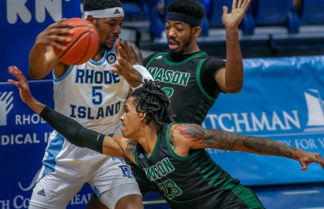 The Rams' Antwon Walker, who had 17 points, protects the ball while looking to pass despite the tight defense of the Patriots' Javon Green and A.J. Wilson on Saturday.
