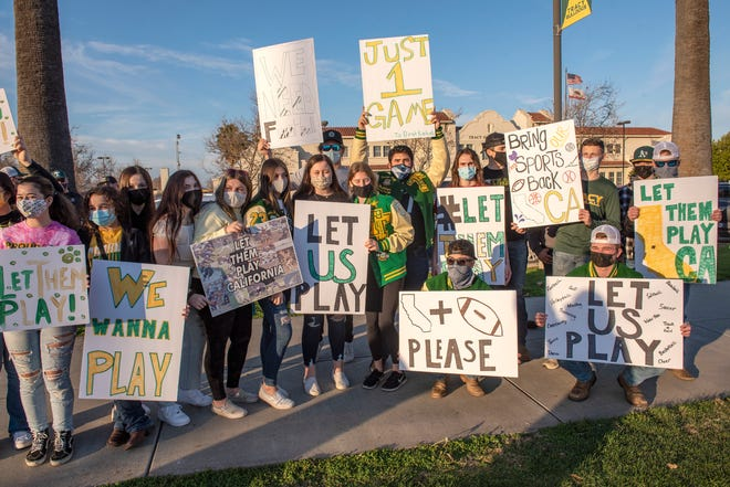 Tracy High school student-athletes and parents hold up signs Friday in front of Tracy High School, joining some 80-plus schools in simultaneous #LetThemPlayCA rallies across the state to support the return of high school sports.