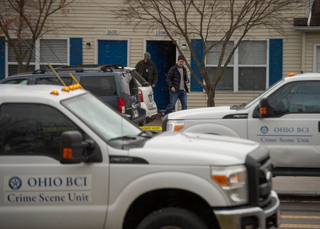 Police personnel exit a duplex at 1596 E. Summit St. in Kent where two officers and a man were shot Saturday.