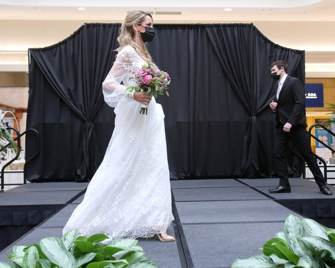Models wearing masks showcase wedding apparel by Lavender Bridal Salon and American Commodore Tuxedo during the 24th annual Belden Village Bridal Show at Belden Village Mall Saturday afternoon. With the pandemic disrupting many wedding plans in 2020, many local engaged couples are eager to proceed with preparing for weddings this year or in 2022.