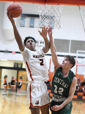 Ardell Banks of Massillon drives to the basket in the first half with pressure from Cade Benjamin of Central Catholic.
