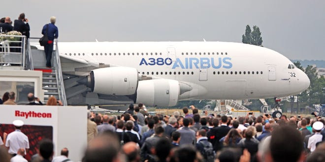 """Visitors watch as an Airbus A380 lands after its demonstration flight at the Paris Air Show in Le Bourget, north of Paris on June 18, 2015. The world's largest commercial jet, the Airbus A380 """"superjumbo"""" is capable of flying up to 800 passengers. It was unveiled in Toulouse, France, on this day in 2005."""