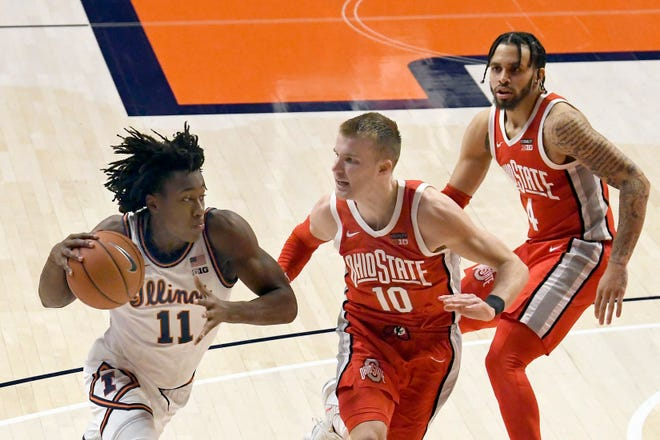 Illinois guard Ayo Dosunmu drives to the basket against Ohio State forward Justin Ahrens (10) and guard Duane Washington Jr. (4) in the second half Saturday in Champaign. (AP Photo/Holly Hart)