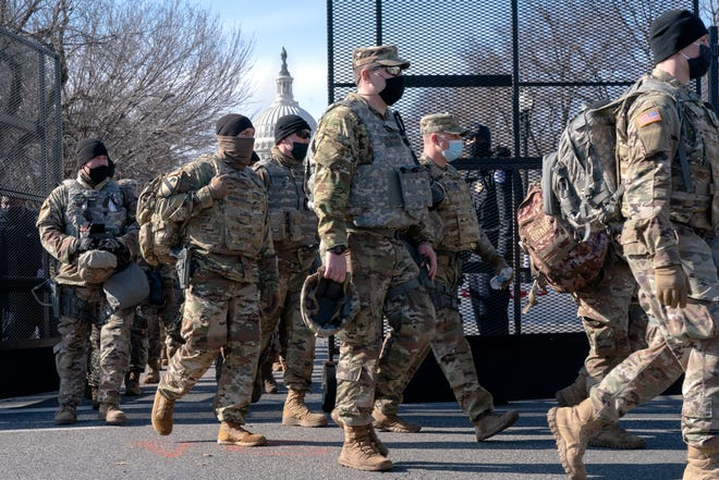 With the U.S. Capitol in the background, members of the National Guard change shifts as they exit through anti-scaling security fencing on Saturday in Washington.