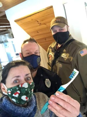 Sandy Binion, left, with West Brookfield Police Officer Craig Charron, center, and Fire Chief Clayton Edwards. The men came to Binion's aid Thursday after she called for help with an unusual problem at her home.