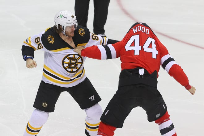 Bruins defenseman Kevan Miller, left, and Devils left wing Miles Wood go at it during the first minute of Saturday's game in New Jersey.