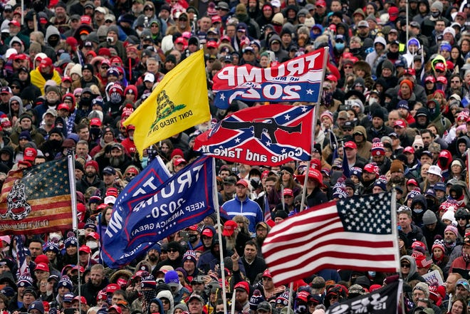 In this Jan. 6  file photo, supporters listen as President Donald Trump speaks as a Confederate-themed and other flags flutter in the wind during a rally in Washington.