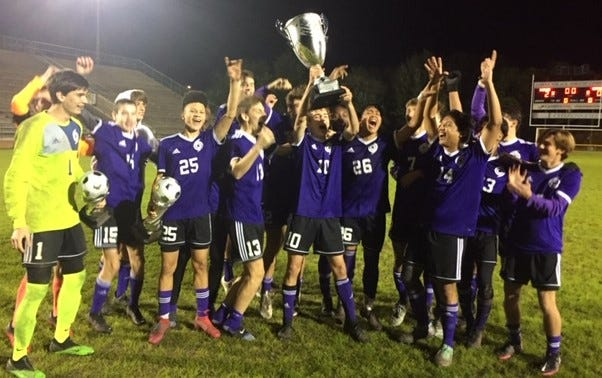 Gainesville High players hold up the Alachua County Cup trophy after Friday's 2-0 win at Citizens Field.