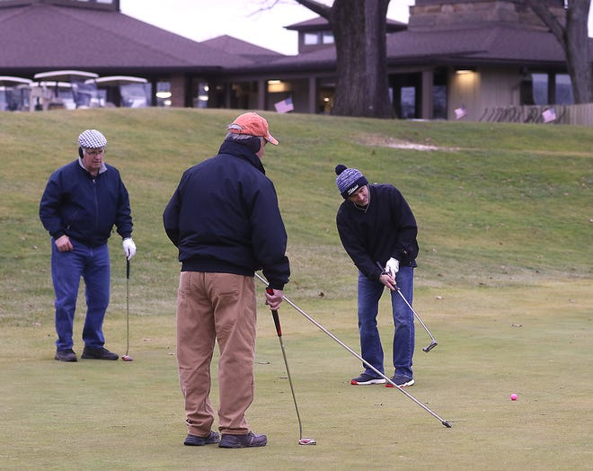 In this Times-Reporter file photo, a group of golfers braved the weather and were putting on the 18th green, with the clubhouse in the background, following a round of golf at Wilkshire Golf Club.