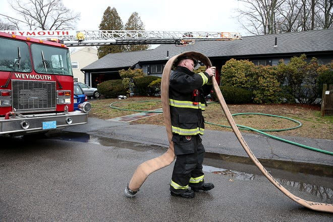 Firefighter Tim Bailey rolls up his hose after they had extinguished a fire at 177 Belmont Street in Weymouth on Saturday, Jan. 16, 2021. Weymouth fire received a call from the homeowner reporting a bedroom fire in the rear of the home. Upon arriving, they faced an extremely hot fire. No injuries were reported at the fire but a black kitten is still missing.