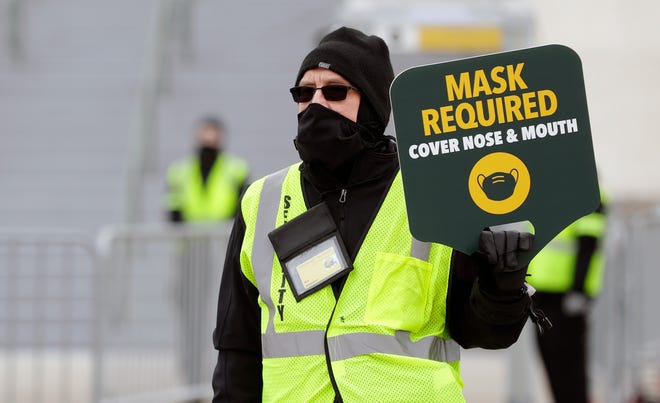 A security guard holds a sign stating 'Masks Required' as a reminder to fans attending the Green Bay Packers vs. Los Angeles Rams playoff on Jan. 16, 2021, at Lambeau Field in Green Bay, Wis.