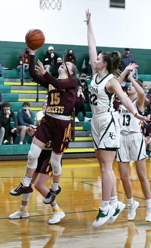 Berne Union senior point guard Emily Blevins shoots a layup over Fisher Catholic's Ellie Bruce Friday night at Fisher Catholic. Berne Union won 57-37.