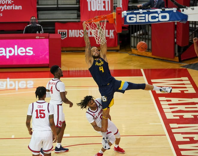 Marquette's Theo John is fouled while attempting a dunk against St. John's.