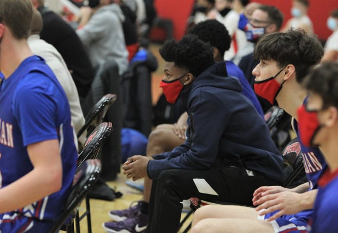 Wisconsin Lutheran's Jordan Glenn supports his teammates from the bench during a game Friday night at Pewaukee. Glenn collapsed on the court during a game at Menomonee Falls on Jan. 9.