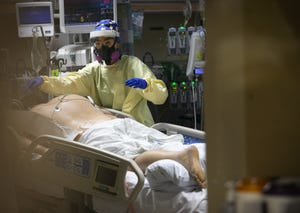 A health care provider tends to a patient that is intubated in one of the COVID-19 units at Valleywise Health Medical Center in Phoenix on Jan. 14, 2021.