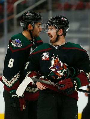 Coyotes' Nick Schmaltz (8) and Conor Garland (83) talk during the second period against the Sharks at Gila River Arena.