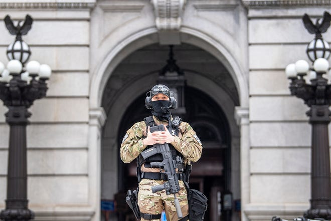 A member of the Pennsylvania Capitol Police guards the entrance to the Pennsylvania Capitol Complex in Harrisburg, Pa. Wednesday, Jan. 13, 2021. State capitols across the country are under heightened security after the Jan. 6 siege of the U.S. Capitol.