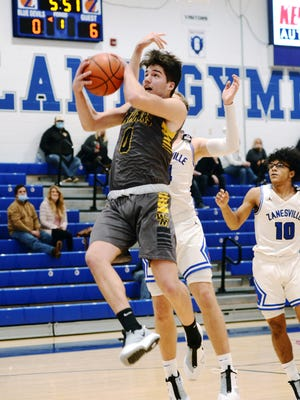 Brent Casterline pulls down a rebound during the first half of Watkins Memorial's 57-46 win against host Zanesville on Jan. 15 at Winland Memorial Gymnasium. Casterline had a game-high 10 rebounds to lead a dominant effort inside for the Warriors.