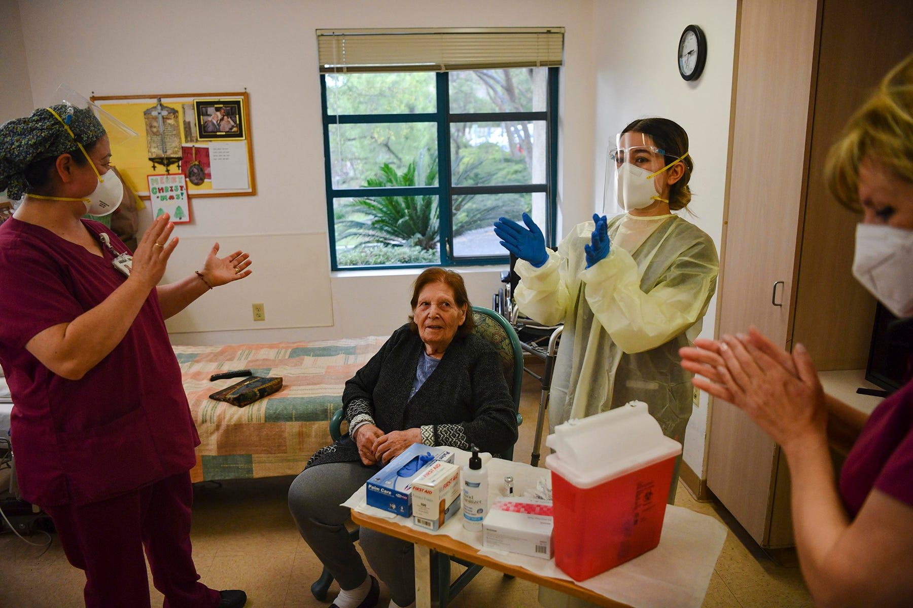 Nurses cheer for resident Tamara Keshishzadeh after she receives Moderna's COVID-19 vaccine.