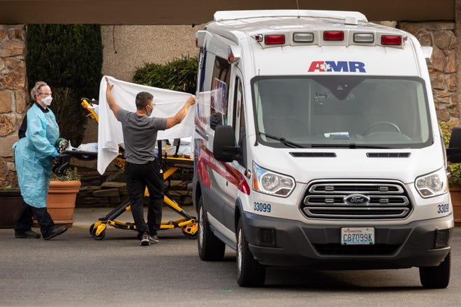 Healthcare workers transport a patient on a stretcher into an ambulance at Life Care Center of Kirkland in Kirkland, Washington on Feb. 29, 2020. By then, dozens of staff and residents at Life Care Center of Kirkland already were reportedly exhibiting coronavirus-like symptoms.