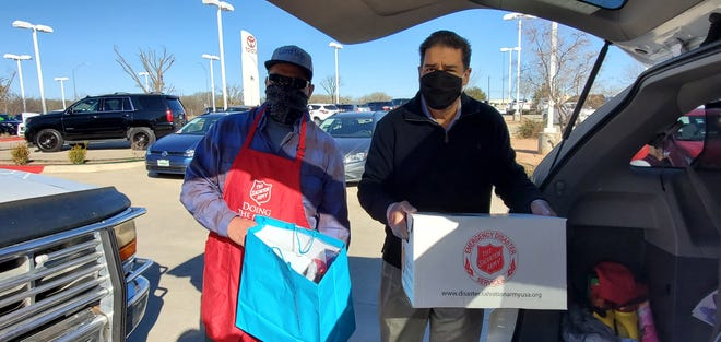 Pastor Roland Nava (left) of the In The Streets Hands up High Ministry and Lost Pines Toyota dealership owner Carlos Liriano (right) load food bags and boxes into cars Jan. 15 during a drive-thru food distribution event at Lost Pines Toyota in Bastrop. [CONTRIBUTED BY THE SALVATION ARMY]