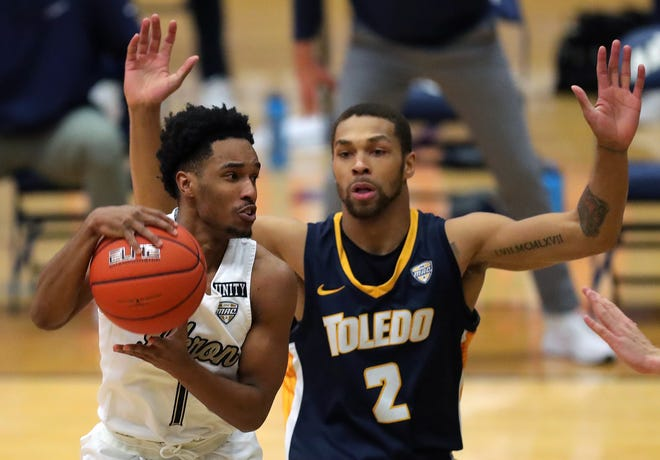 University of Akron guard Loren Cristian Jackson (1) drives to the basket past Toledo Rockets forward Setric Millner Jr. (2) during the first half of the Zips' 95-94 win on Jan. 16 in Akron. UA will go for the regular-season sweep Tuesday night in Toledo. [Jeff Lange/Beacon Journal]