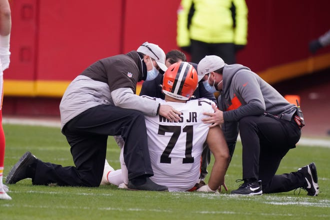Browns offensive tackle Jedrick Wills Jr. is helped off the field after being injured during the first half of an NFL divisional-round playoff game against the Kansas City Chiefs, Sunday, Jan. 17, 2021, in Kansas City. [Charlie Riedel/Associated Press]