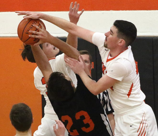 Marlington's Tommy Hippely, right, and Ben Yoder, left, battle with Howland's Gabe Badea (23) for a Tiger rebound during action at Marlington High School Saturday, January 16, 2021.