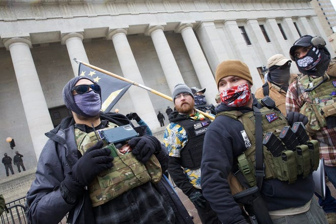 Henry Locke, in a red Hawaiian mask, identified himself as the Statehouse protest organizer and a 'boogaloo' from central Ohio. He said he's there to be peaceful and not aligned with a political party.