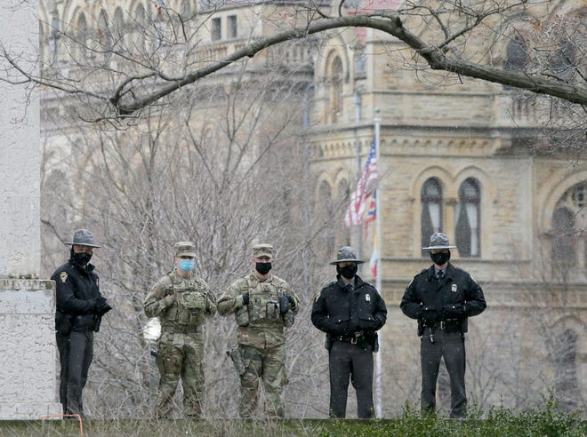 Ohio State Patrol officers and members of the Ohio National Guard watch the grounds during a protest on Sunday at the Ohio Statehouse in downtown Columbus, Oh., on January 17, 2021.